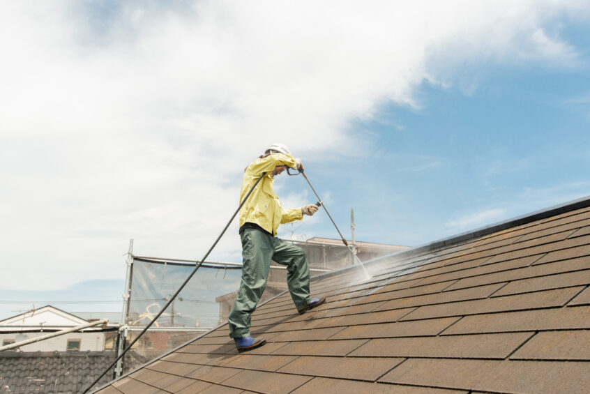 Worker is cleaning for algea & moss on asphalt roof systems